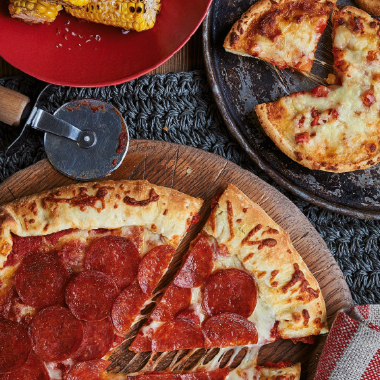 pizza on a wooden block with pizza cutter